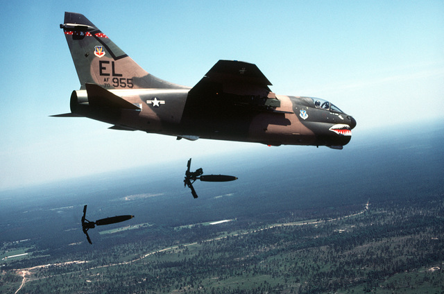 AN air-to-air right side view of an A-7D Corsair II aircraft releasing Mark 82 high-drag bombs over a range. The aircraft is assigned to the 76th Tactical Fighter Squadron, 23rd Tactical Fighter Wing