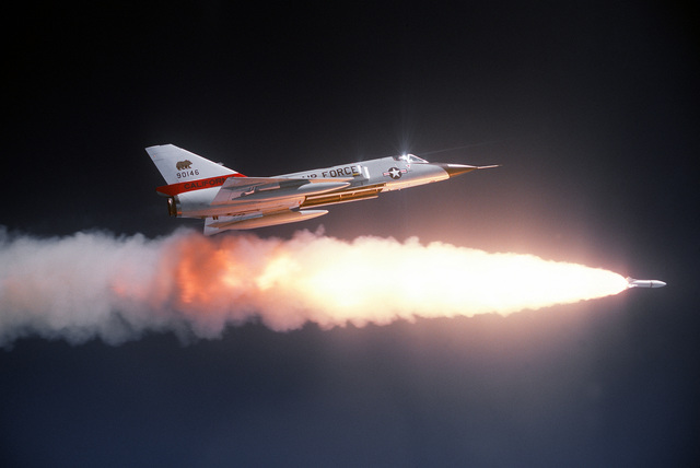 AN air-to-air right side view of an F-106 Delta Dart aircraft after firing an ATR-2A missile over a range. AN auxiliary fuel tank is on each wing. The aircraft is assigned to the 194th Fighter Interceptor Squadron, California Air National Guard