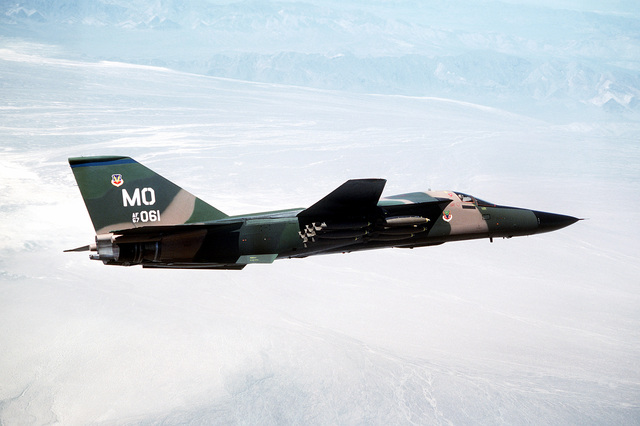 An air-to-air right side view of an F-111 aircraft banking to the left over the Nellis Air Force Base range. The aircraft, assigned to the 391st Tactical Fighter Training Squadron (TFTS), 366th Tactical Fighter Wing (TFW), is carrying 24 Mark 82 low-drag bombs