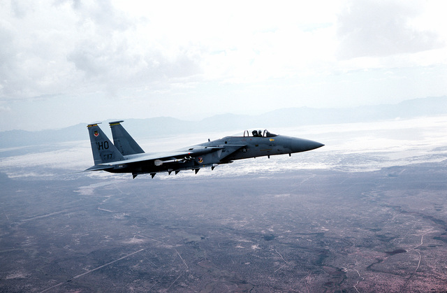 AN air-to-air right side view of an F-15 Eagle aircraft of the 49th Tactical Fighter Wing carrying four AIM-9 Sidewinder and AIM-7 Sparrow missiles