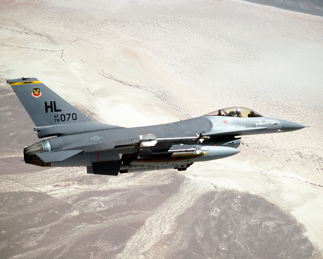 AN air-to-air right side view of an F-16 Fighting Falcon aircraft banking to the left over a range. One AIM-9L Sidewinder, one AIM-9J Sidewinder, one 2,000-lb. MK-84 bomb and an auxiliary fuel tank are on each wing. AN ALQ-119 electronic countermeasures pod is mounted on the centerline. The aircraft is assigned to the 4th Tactical Fighter Squadron, 388th Tactical Fighter Wing