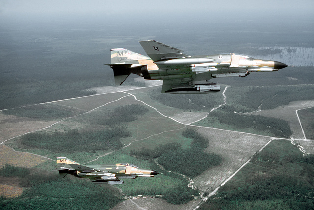 AN air-to-air right side view of two F-4E Phantom II aircraft banking to the left over a range. Two AGM-65 Maverick missiles are loaded on each wing of both aircraft. AN AN/ALQ-119 electronic countermeasures pod is mounted on the left side of each fuselage. The aircraft are assigned to the 347th Tactical Fighter Wing