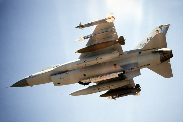 AN air-to-air view of the underside of an F-16 Fighting Falcon aircraft flying over a range. One AIM-9L Sidewinder, one AIM-9J Sidewinder, one 2,000-pound Mark 84 bomb and an auxiliary fuel tank are on each wing. AN ALQ-119 electronic countermeasures pod is mounted on the centerline. The aircraft is assigned to the 4th Tactical Fighter Squadron, 388th Tactical Fighter Wing