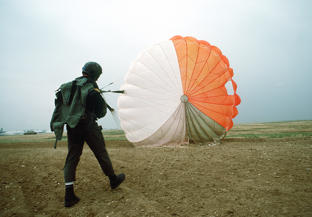 An American jumper prepares to gather his parachute up after landing. The man is taking part in Sarex '80, a joint pararescue exercise involving the United States and Canada