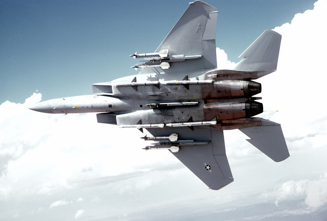 Bottom view of an F-15 Eagle aircraft armed with AIM-9 Sidewinder and AIM-7 Sparrow missiles, in flight Wing