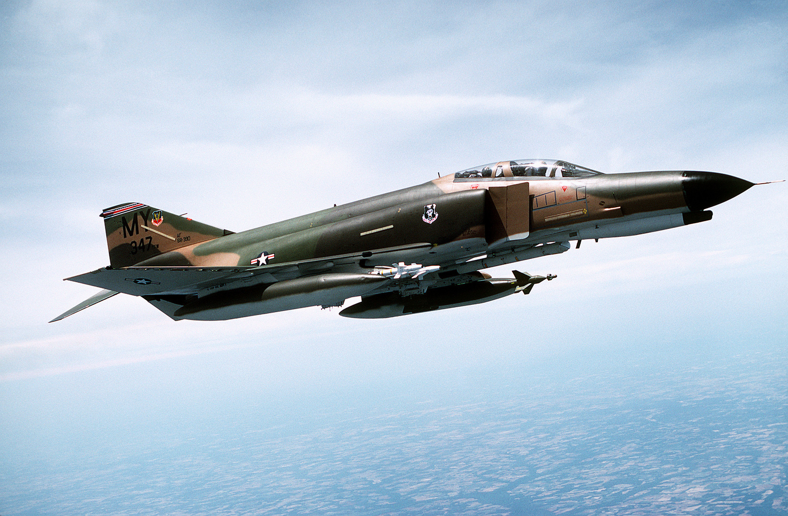 F-4E Phantom II aircraft from the 347th Tactical Fighter Wing. The aircraft is carrying an inboard 2,000-pound GBU-10 laser guided bomb, a Pave Spike laser designator, and two inboard AIM-9J Sidewinder missiles (left side to right)