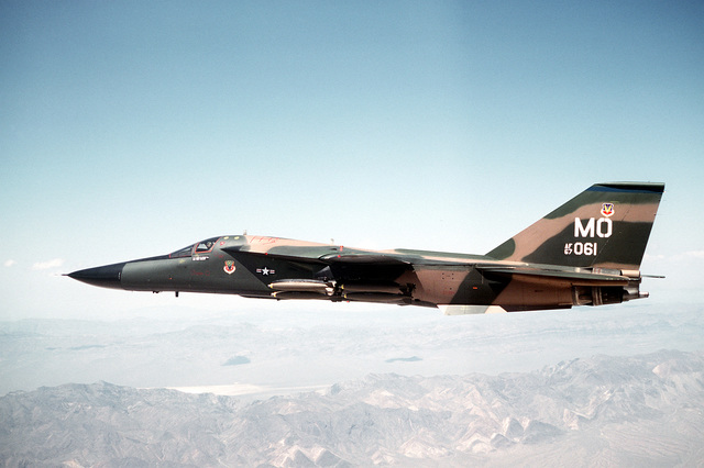 Left side view of an F-111 aircraft in flight over the Nellis Air Force Base range. The aircraft, assigned to the 391st Tactical Fighter Training Squadron (TFTS), 366th Tactical Fighter Wing (TFW), is carrying 24 Mark 82 low-drag bombs