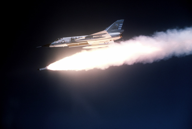 Low angle left side view of an F-106 Delta Dart aircraft of the 102nd Fighter Interceptor Wing firing an AIR-2A Genie air-to-air missile over the Tyndall Air Force Base range