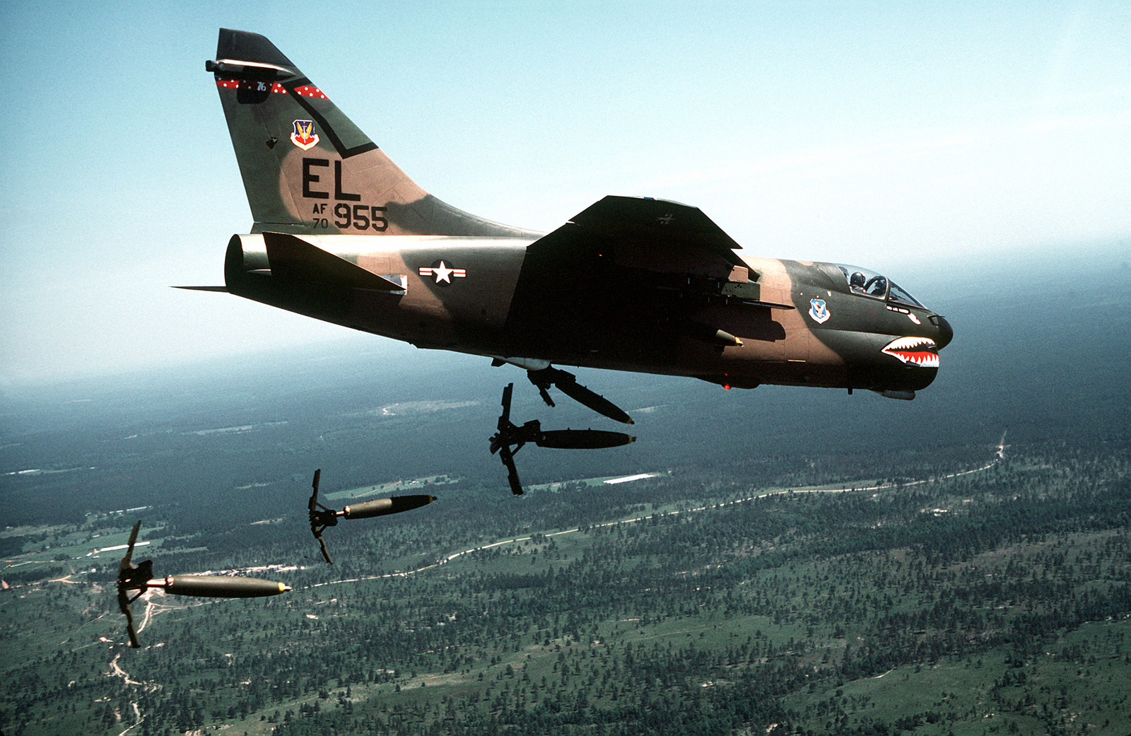 Low angle right side view of an A-7 Corsair II aircraft of the 76th Tactical Fighter Squadron, 23rd Tactical Fighter Wing, airdropping Mark 82 hi-drag bombs over the Tyndall Air Force Base range