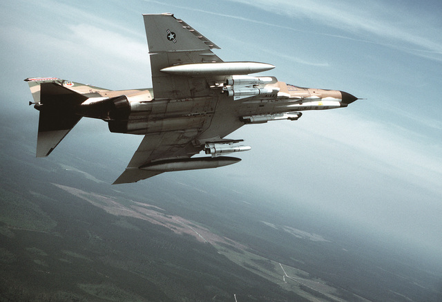 Low angle right side view of an F-4E Phantom II aircraft of the 347th Tactical Fighter Wing carrying four AGM-65A Maverick missiles in flight over the Tyndall Air Force Base range