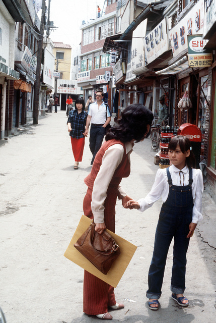 Ms. Tae Sun Pak (left), a social worker employed by the Osan Air Base Chapter of the Amerasian Association, talks to a child of a Korean woman and an American serviceman