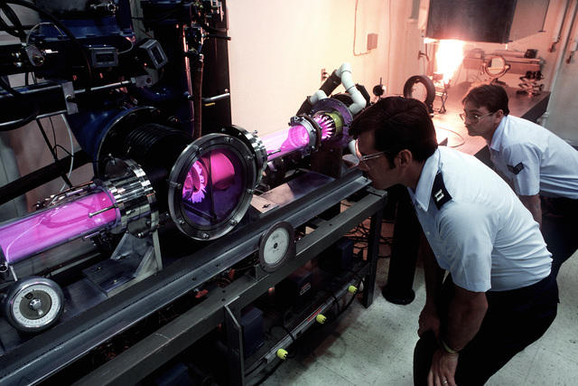 Two laser engineering technicians conduct an experiment with an electric discharge laser beam in the laser laboratory of the Air Force Weapons Laboratory. The lasers are used in laboratory experiments to determine the laser interaction with various types of materials