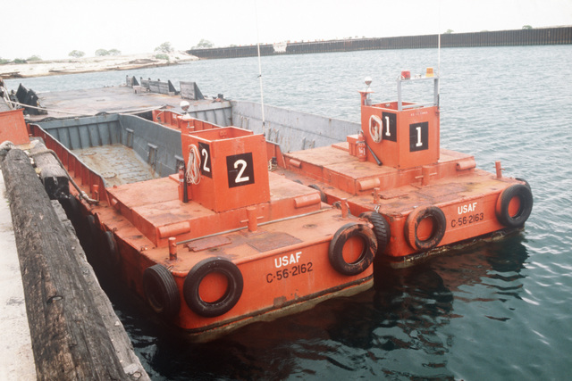 Two US Air Force LCM 6 landing craft docked at a pier