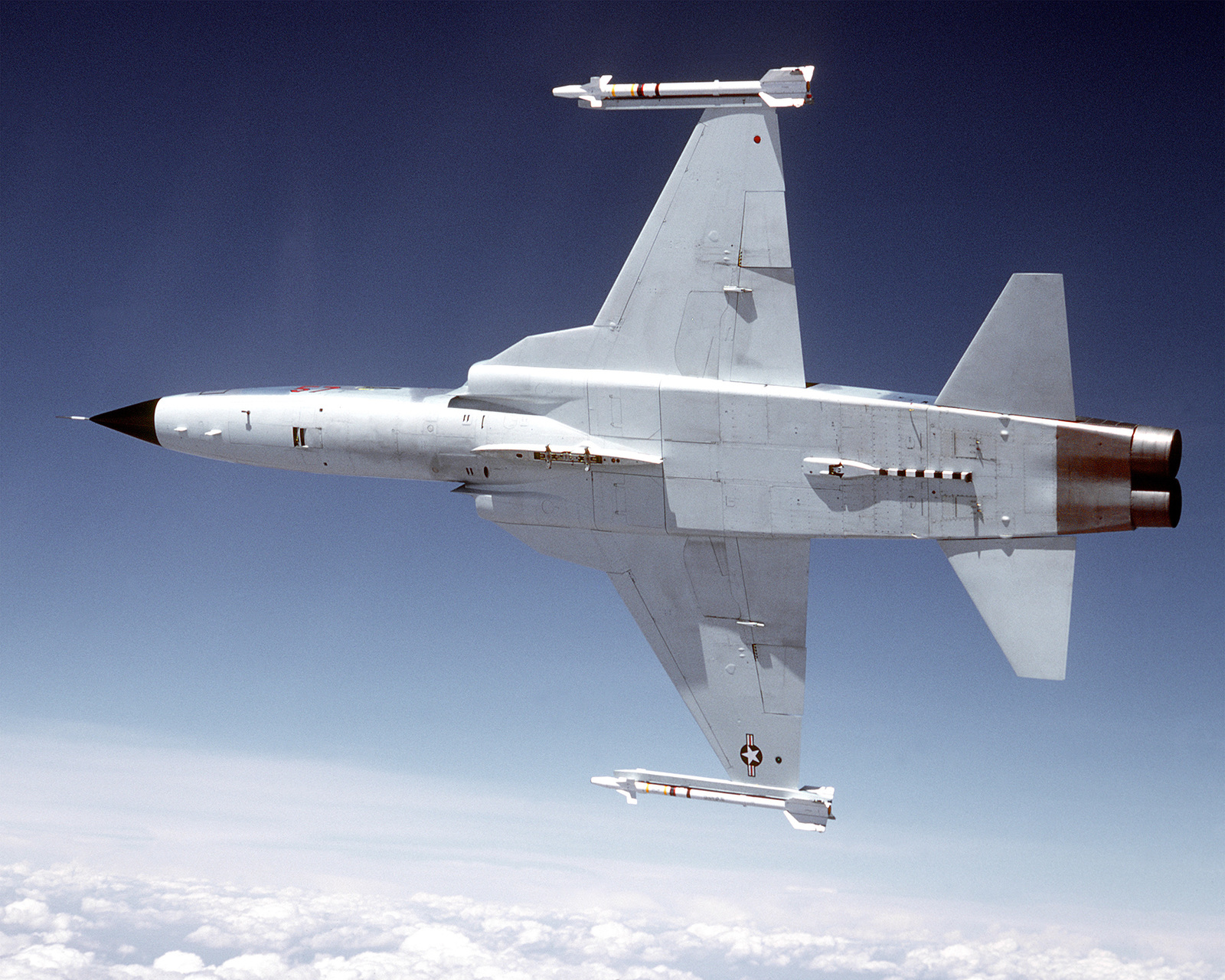 View of the bottom of an F-5 Tiger II aircraft as the jet banks to the right over a range. One AIM-9J Sidewinder missile is on each wing tip. The aircraft is assigned to the 57th Fighter Weapons Wing