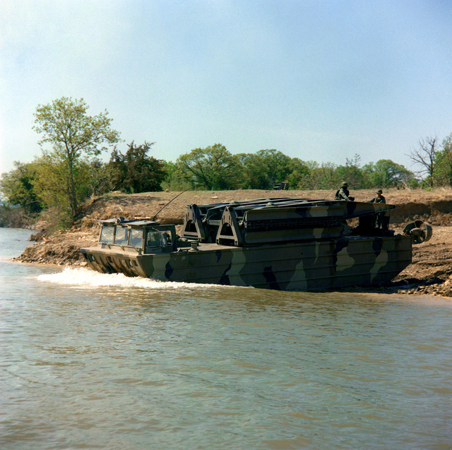 A section of a mobile assault bridge operated by Company E, 1ST Engineer Battalion enters the water during a river crossing exercise