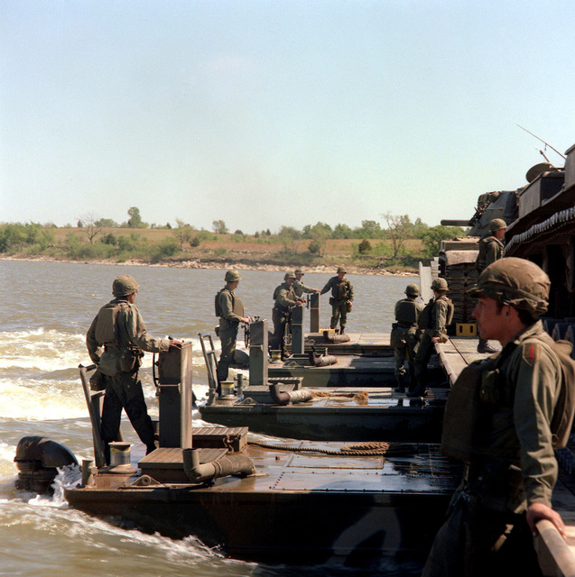 Members of Company E, 1ST Engineer Battalion transport tanks across a river aboard a mobile assault bridge during a river crossing exercise