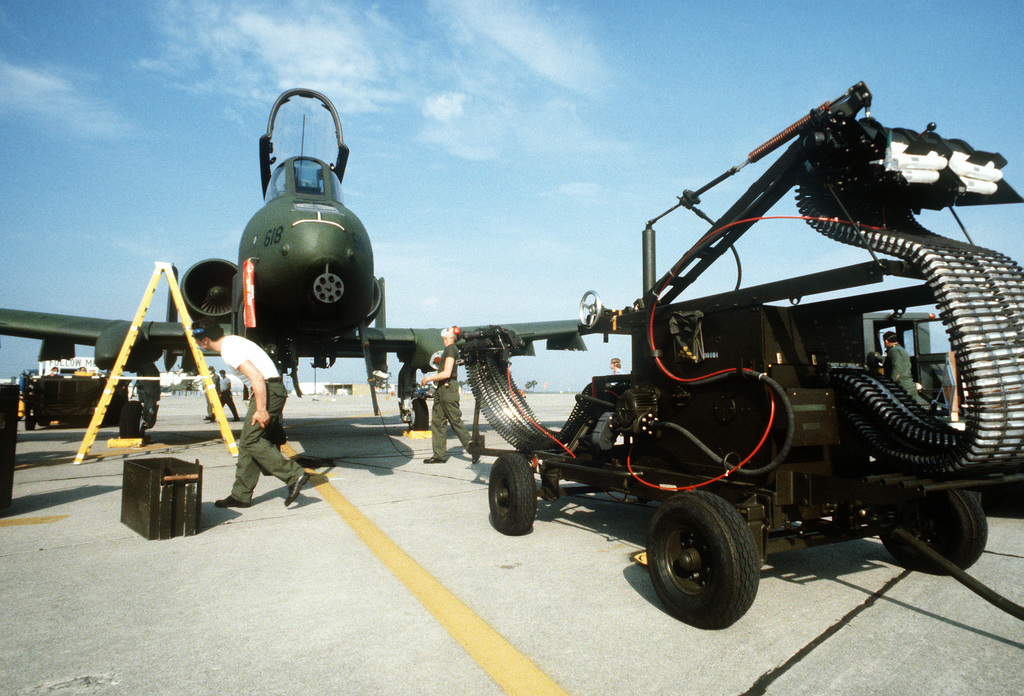 AN automatic loader is moved into position for loading the 30mm nose gun on an A-10 Thunderbolt II aircraft during operational readiness inspection at Travis Field