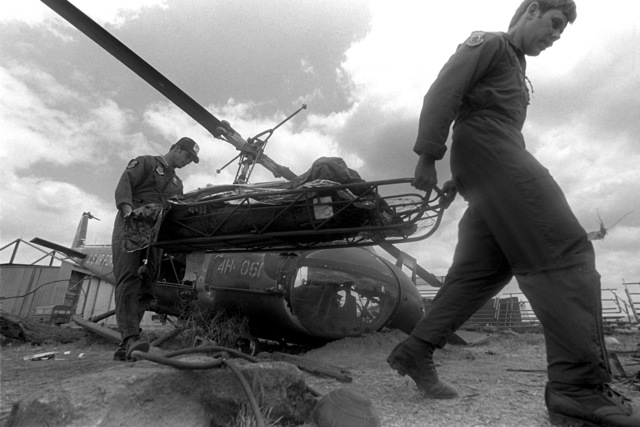 """Pararescuemen use a litter to remove one of the """"victims"""" from a simulated helicopter crash site during the medical exercise phase of SAREX '80"""