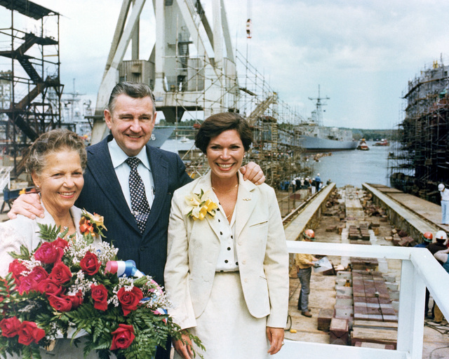Dorothy M. Flatley, sponsor, left, John F. Sullivan Jr., president, Bath Iron Works, and Mrs. Nancy G. Flatley stand in front of the ways that the Oliver Hazard Perry class guided missile frigate USS FLATLEY (FFG 21) recently slid down. The Flatley is in the background