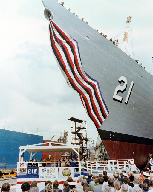 The bow of the USS FLATLEY (FFG 21) towers over guest speaker Rear Admiral Kleber S. Masterson Jr., assistant deputy commander, Surface Warfare and Anti-air Warfare Systems, Naval Sea Systems Command, during the launching ceremony for the Oliver Hazard Perry class guided missile frigate
