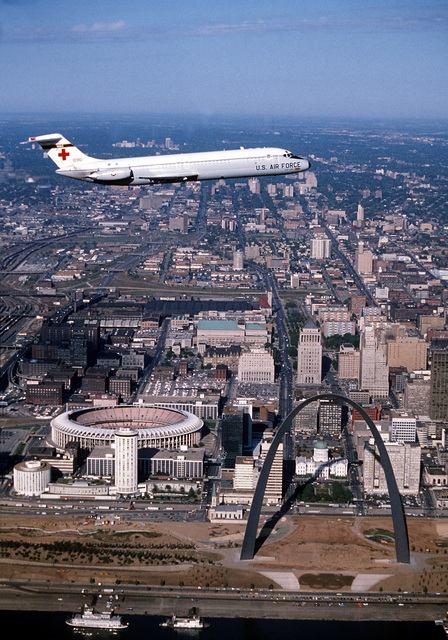 """A right side view of a C-9 Nightingale aircraft in-flight, with the Checkerdome and St. Louis Arch in the background. The aircraft is from the 375th Aeromedical Airlift Wing, participating in training. The photo, entitled """"St. Louis Fly By,"""" won second place in the AAVS PHOTO Contest Entry, Sept. 1980"""