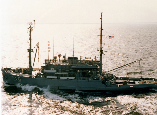 An aerial port beam view of the salvage ship USS HOIST (ARS 40) underway
