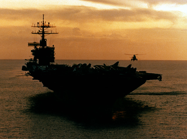 A bow view of the nuclear-powered aircraft carrier USS NIMITZ (CVN 68). A helicopter hovers over the forward flight deck