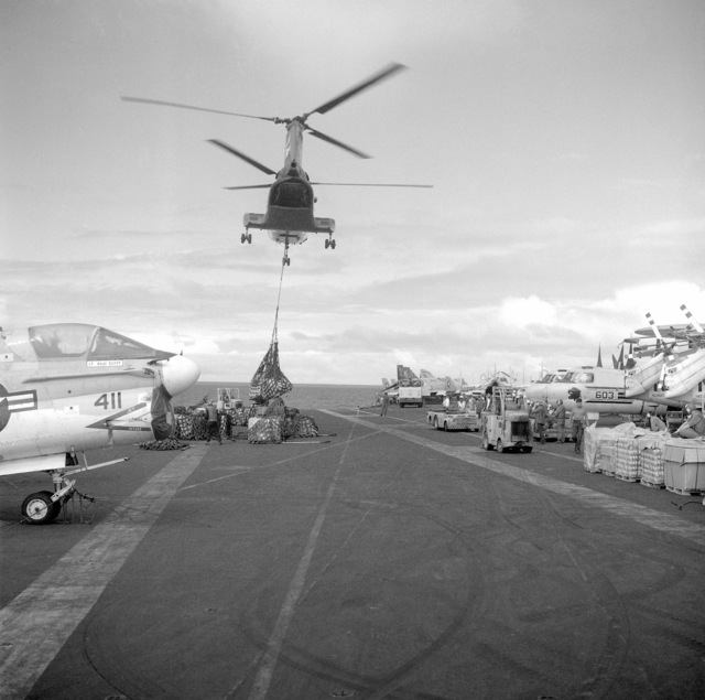 A CH-46 Sea Knight helicopter delivers supplies to the deck of aircraft carrier USS CORAL SEA (CV 43). On the left is an A-7E Corsair II light attack aircraft. The CORAL SEA is returning to its home port at Naval Air Station Alameda, California after an Indian Ocean deployment