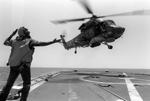 A flight deck crewman directs the pilot of an SH-2 Seasprite helicopter as the helicopter lands aboard the frigate USS DONALD B. BEARY (FF-1085). The helicopter is from Light Helicopter Anti-submarine Squadron 32 (HSL-32)
