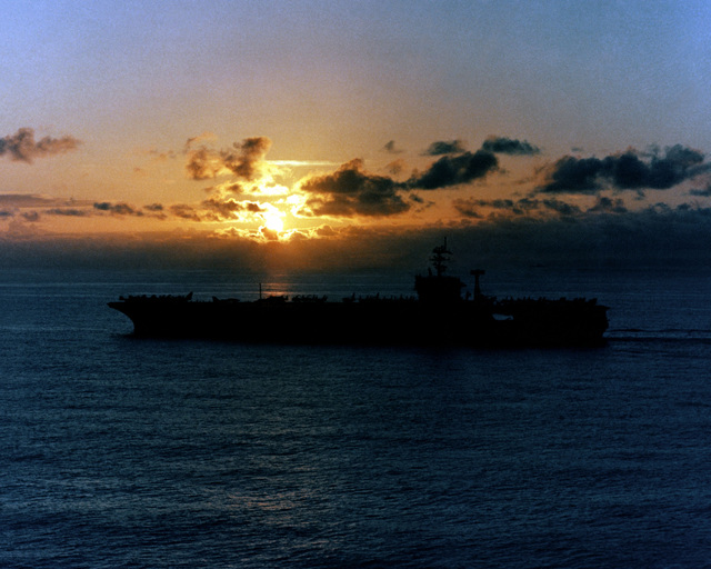 A port beam view of the nuclear-powered aircraft carrier USS NIMITZ (CVN 68) silhouetted against the setting sun