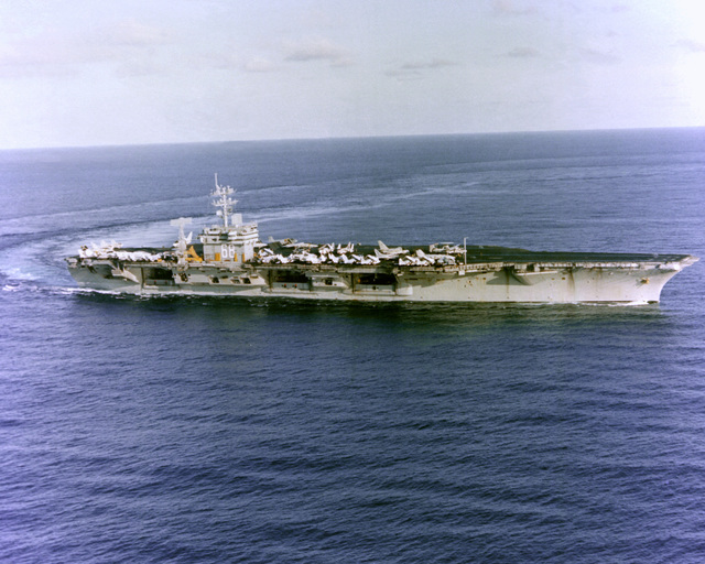 A starboard bow view of the nuclear-powered aircraft carrier USS NIMITZ (CVN-68) executing a turn