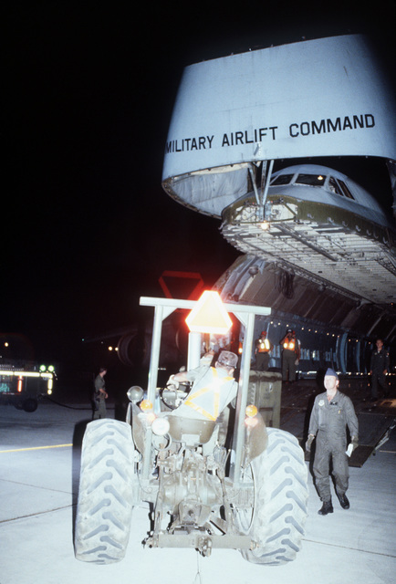 An airman uses a forklift to load cargo onto a C-5A Galaxy aircraft at night during exercise PROUD PHANTOM