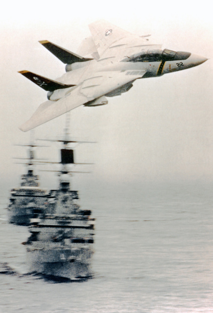 An F-14 Tomcat aircraft, with its wings swept back, makes a low altitude turn above two Virginia Class nuclear-powered guided missile cruisers that are underway