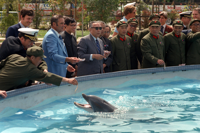 Chai Zemien, center, Chinese ambassador to the United States, and members of the delegation from the People's Republic of China feed a dolphin during their tour of Sea World