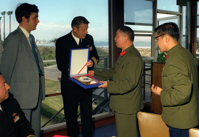 A member of the delegation from China receives a gift from a Navy vice admiral