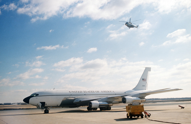 A VC-137 Stratoliner aircraft parked on the flight line as an HH-53B Super Jolly helicopter hovers overhead