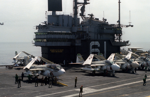 An aerial view of an A-6A Intruder aircraft and a EA-6B Prowler aircraft lined up on the flight deck of the aircraft carrier USS RANGER (CV-61)