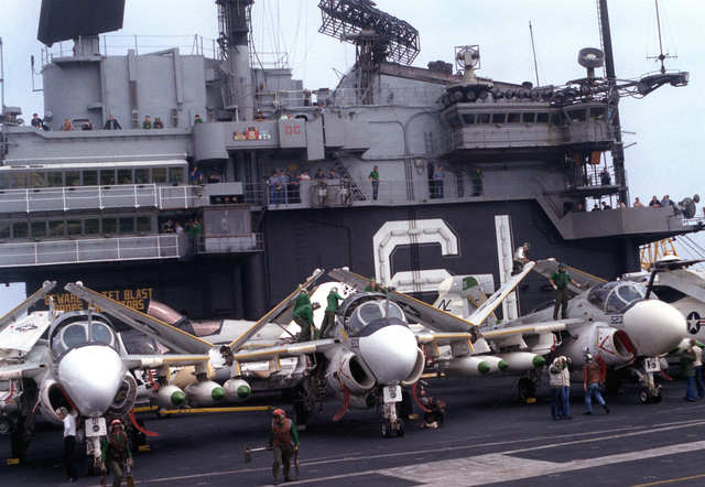 An EA-6A Intruder and EA-6B Prowler aircraft loaded with bombs are lined up on the flight d deck of the aircraft carrier USS RANGER (CV-61)