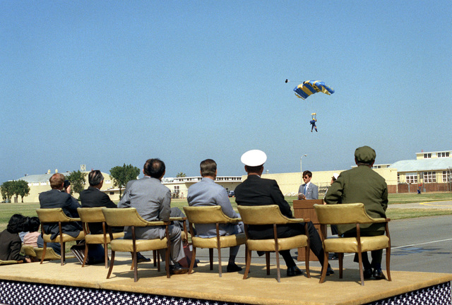 Vice Premier Geng Biao of China and U.S. Navy officials watch a parachute demonstration