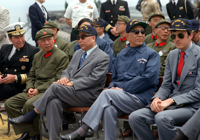 Vice Premier Geng Biao of China, in the blue jacket, and the Chinese ambassador sit with U.S. Navy officials aboard the aircraft carrier USS RANGER (CV-61). They are waiting for the start of the air and sea demonstration