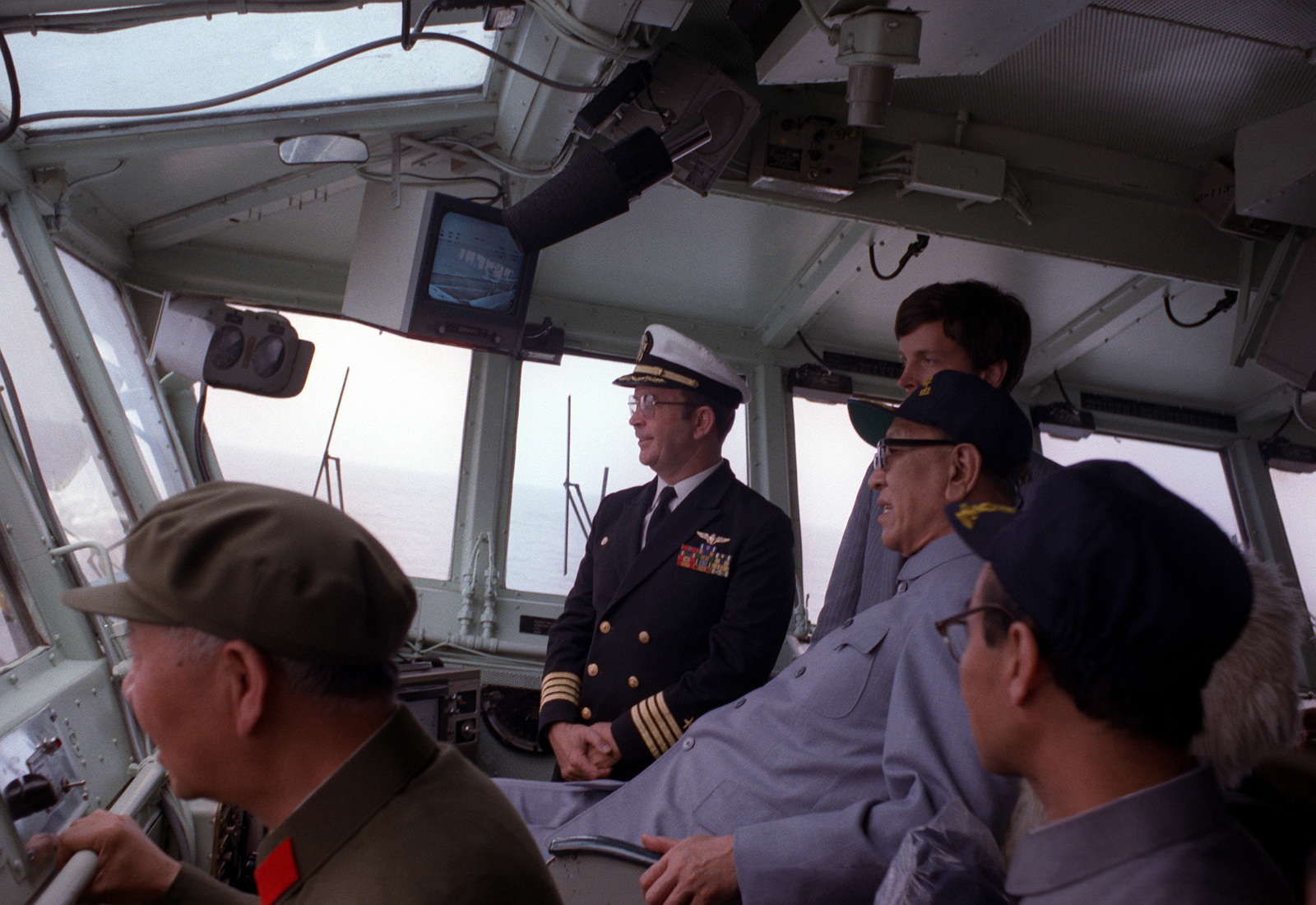 Vice Premier Geng Biao, People's Republic of China, sits in the captain's chair during his tour of the aircraft carrier USS RANGER (CV-61). The ship's captain, CAPT Roger Box, is standing to his right