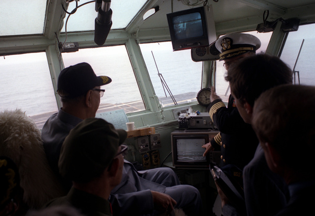 Vice Premier Geng Biao, People's Republic of China, sits in the captain's chair aboard the aircraft carrier USS RANGER (CV-61) as the captain of the ship, CAPT Roger Box, explains some of the ship's procedures
