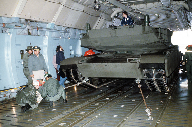 A front view of an XM-1 Abrams tank being secured aboard a C-5A Galaxy aircraft