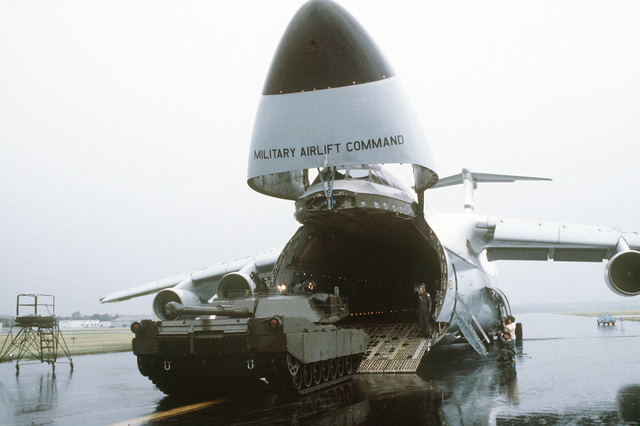 A right rear view of an XM-1 Abrams tank being driven into a C-5A Galaxy aircraft