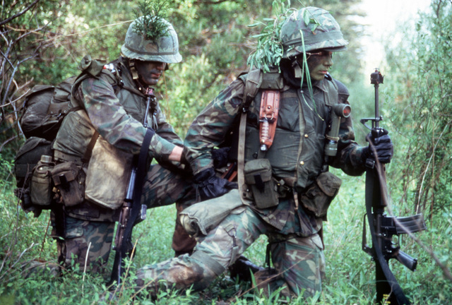 A close view of a combat-ready Marine officer candidate as he checks the backpack of another candidate. Both of them are wearing camouflage paint on their faces. The Marines are students of The Basic School for Marine Officers Combat Training