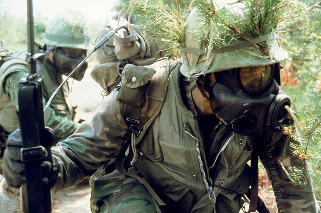 A close view of a combat-ready Marine officer candidate wearing a field protective mask as he waits for the signal to move forward. This Marine is a student of The Basic School for Marine Officers Combat Training