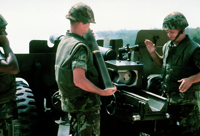 A right rear view of the gunner as he adjusts the sight of a