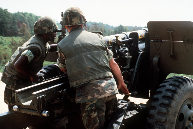 A right rear view of the gunner as he adjusts the sight of a 105mm howitzer gun from the Artillery Demonstration Unit. The assistant gunner looks on. This gun section is preparing to fire in support of The Basic School for Marine officer candidates field training