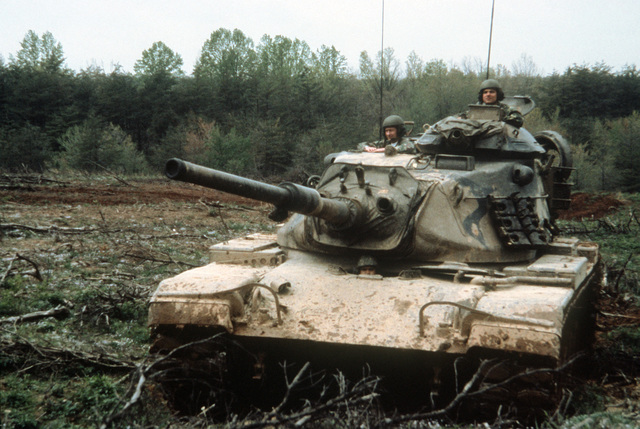 An M-60A1 tank crew from the Artillery Demonstration Unit gives support to Marine officer candidates who are training in combat tactics