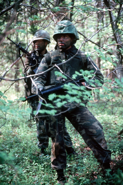 Two combat-ready Marine officer candidates stop and look the terrain over. These Marines, who have camouflage paint on their faces, are students of The Basic School for Marine Officers Combat Training